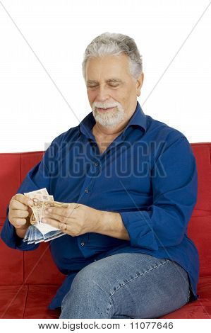 elderly man on the couch with money in hand