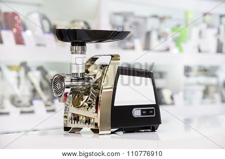 Electric mincer or grinder at retail store shelf, defocused background
