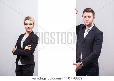 Two Businessmen: A Man And A Woman Are Standing On Either Side Of A Billboard In White, Looking At T