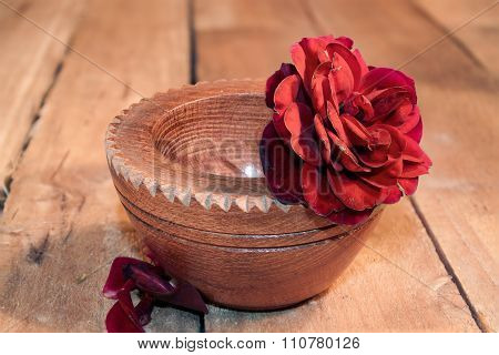 red rose in wooden bowl