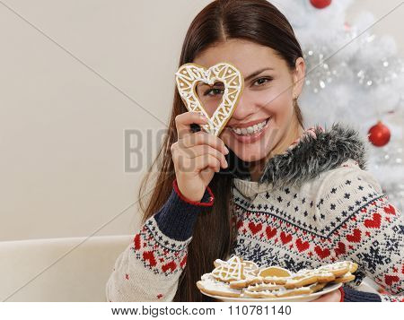 Attractive Young Woman Having Fun With Home Cookies On Christmas Tree Background