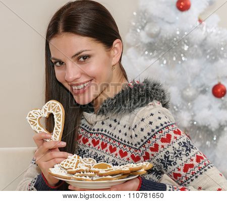 Attractive Young Woman With Home Cookies Near Christmas Tree