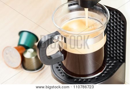 Single-serving coffee machine dispenses  espresso in a glass cup  with coffee capsules in background