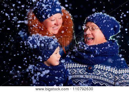 Smiling Grandparent And Grandson Having Fun Under The Snow