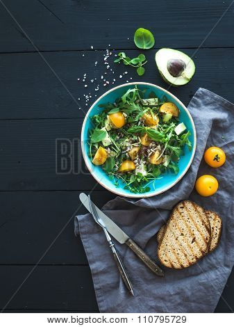 Bowl of green salad with avocado, arugula, cherry tomatoes and sunflower seeds, grilled bred slices,