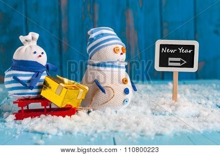 Signpost of the New Year and two Snowman with red sled stand near direction sign. Happy new year pos