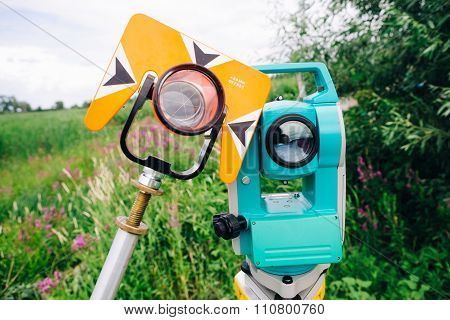 Orange Theodolite Prism And Blue Surveying Equipment Total Station On  A Background Of Lake