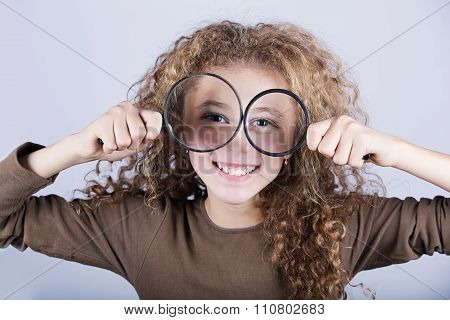 Funny portrait of cute little girl looking through magnifying glass