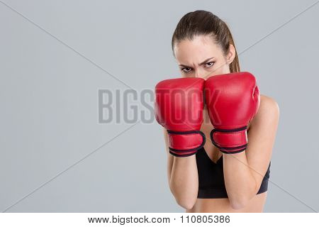Strong intense young fitness woman covered her face with boxing gloves over grey background