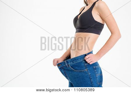 Young sportswoman with beautiful body in old big jeans showing how much weight she lost over white background