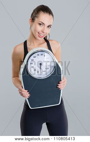 Portrait of happy lovely cute fitness girl in sportwear with weigh scale over grey background