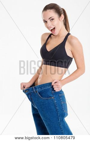 Amazed happy young fitness woman became skinny and wearing old jeans over white background