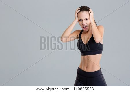 Crazy hysterical shouting fitness girl in black top and leggings isolated over grey background