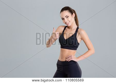 Happy beautiful young sportswoman in black tracksuit showing thumbs up over grey background