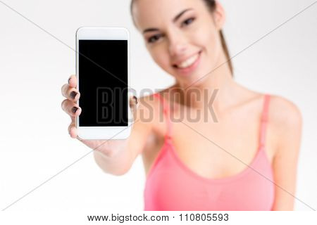 Happy pretty fitness girl in pink top showing cellphone with blank screen over white background