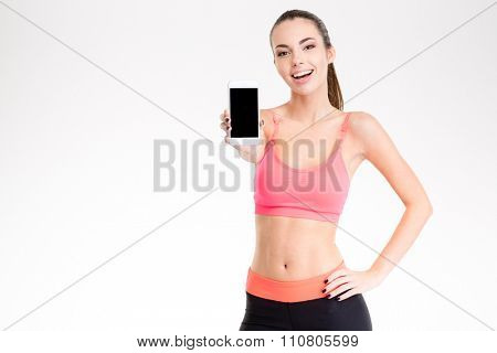 Attractive cheerful young fitness woman showing blank smartphone screen isolated over white background