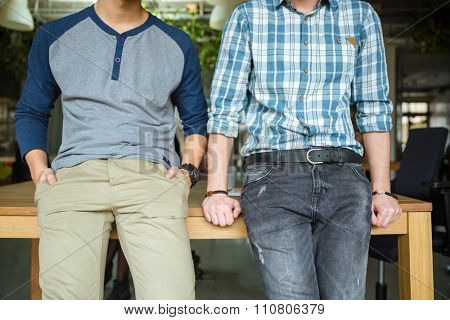 Two male standing and waiting leaning on the wooden table