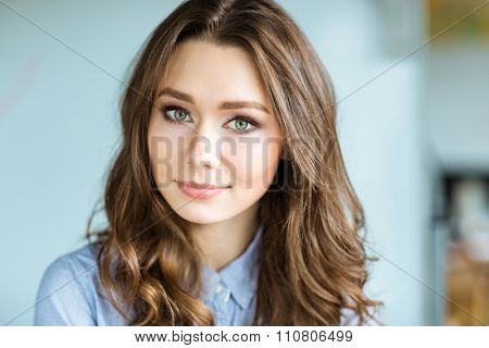 Portrait of attractive thoughtful young curly woman looking at camera