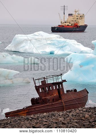 Ship wreck on Arctic coast with icebergs and icebreaker on background