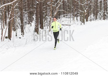 Young fit woman running outdoors in a park on cold winter day.