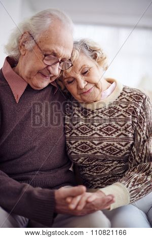Devoted couple of pensioners in sweaters holding by hands