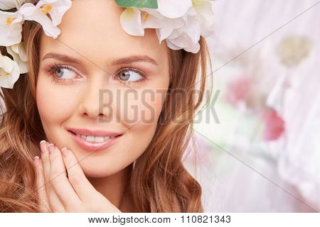 Charming young woman with natural make-up looking sideways