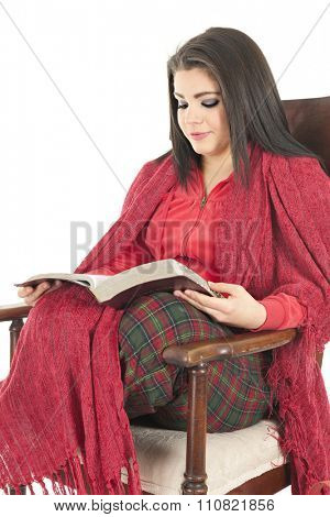 A beautiful teen girl cozied in her Christmas pajamas and a red blanket in a rocking chair reading her Bible.  On a white background.