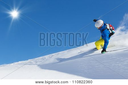Man skier running downhill on sunny slope