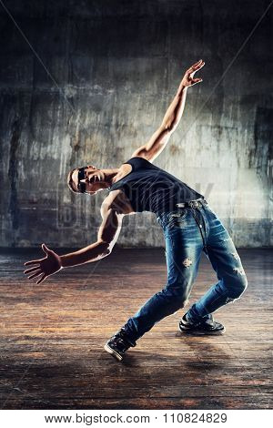 Young man break dancer standing in dodge bullets pose on old wall background