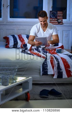Young man in bed using tablet computer at night.