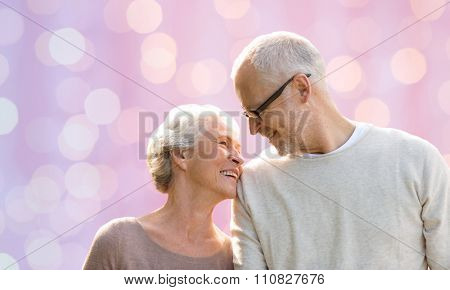family, love, age and old people concept - happy senior couple looking at each other over pink holidays lights background