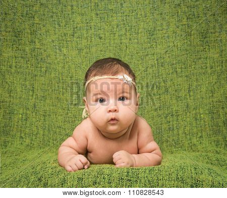 two-month-old girl with decoration on a head lies on a green background