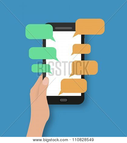 Hand holding black smartphone with chat bubbles.