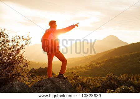 Hiker stands on the cliff over the sunrise