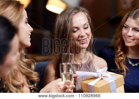 celebration, friends, bachelorette party, birthday and holidays concept - happy women with champagne glasses and gift box at night club