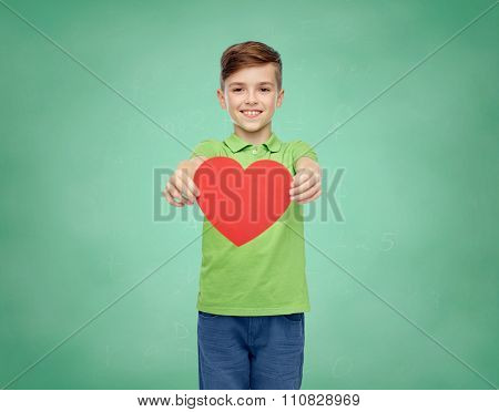 childhood, love, charity, health care and people concept - happy smiling boy in green polo t-shirt holding blank red heart shape over green school chalk board background
