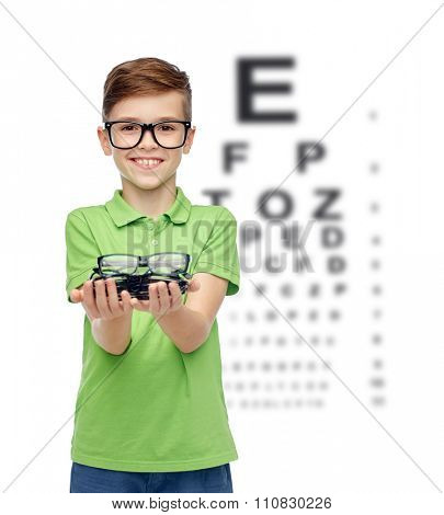 childhood, vision, eyesight, health care and people concept - happy smiling boy in green polo t-shirt with eyeglasses over eye chart background