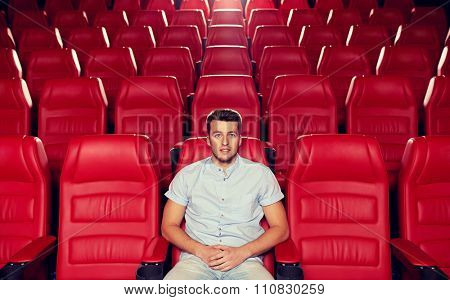cinema, entertainment and people concept - happy young man watching movie alone in empty theater auditorium