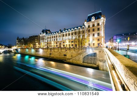 The Petit Pont And Buildings Along The Seine At Night, In Paris, France.