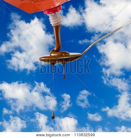 Image Of Liquid Chocolate On A Spoon Against The Sky