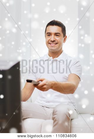 home, people, technology and entertainment concept - smiling man with remote control watching tv at home over snow effect