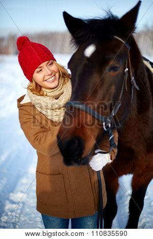 Smiling beautiful woman take care of horse