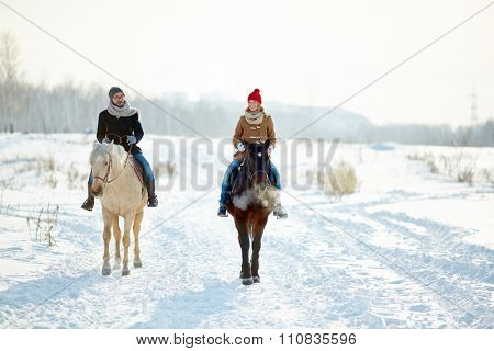 Young couple enjoying horse riding together