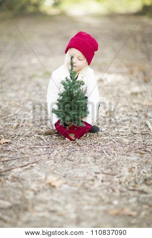Baby Girl In Red Mittens and Cap Near Small Christmas Tree Outdoors.