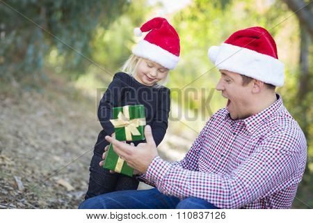 Happy Father Giving Young Daughter A Christmas Gift Outdoors.