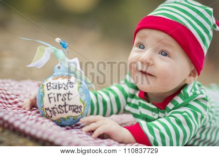 Beautiful Infant Baby On Blanket With Babys First Christmas Ornament.