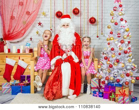 Happy Girls And Santa Claus Sitting On A Bench In A Christmas Setting