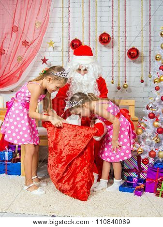 Girls Looking At A Gift Bag With Gifts That Brought Santa Claus