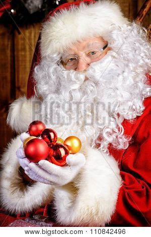 Good old Santa Claus with Christmas balls at his wooden house.