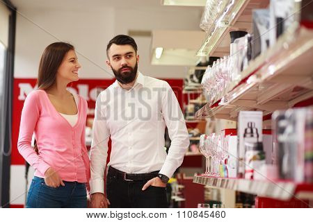Young Couple In The Store On Background Of Shelves With Wine Glasses